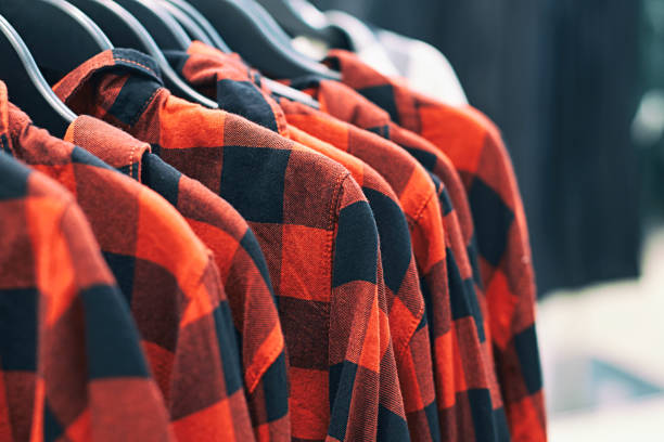 Men red plaid shirt on hangers in a retail clothes store. Fashion trend concept. Interior of clothes store. plaid shirt stock pictures, royalty-free photos & images