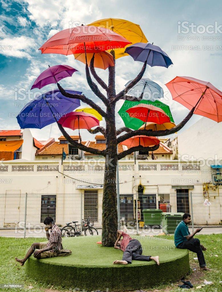 Men resting under umbrella trees in little India Singapore stock photo