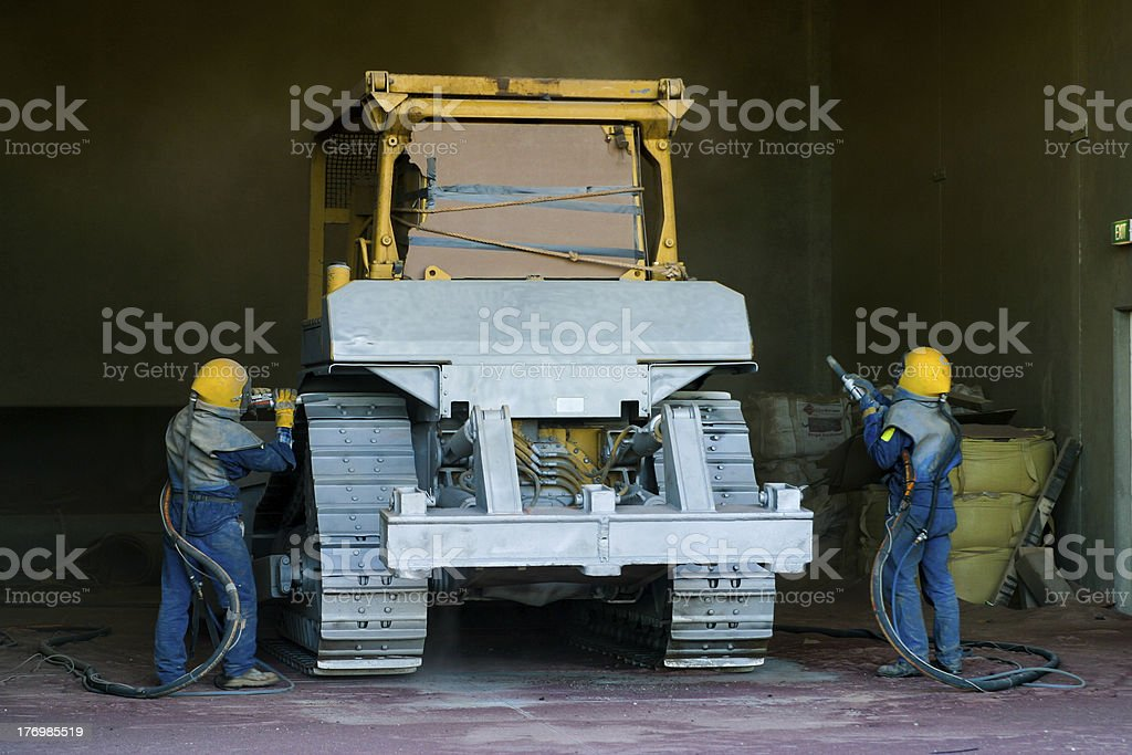 Men sandblast bulldozer stock photo