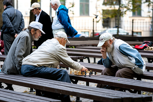 Men seated on park benches and playing chess.