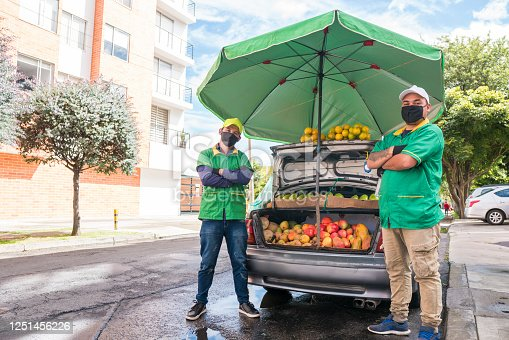 Two Latino men ages 25-35 selling fruits and vegetables in a car while wearing face masks to protect themselves from the COVID-19 virus