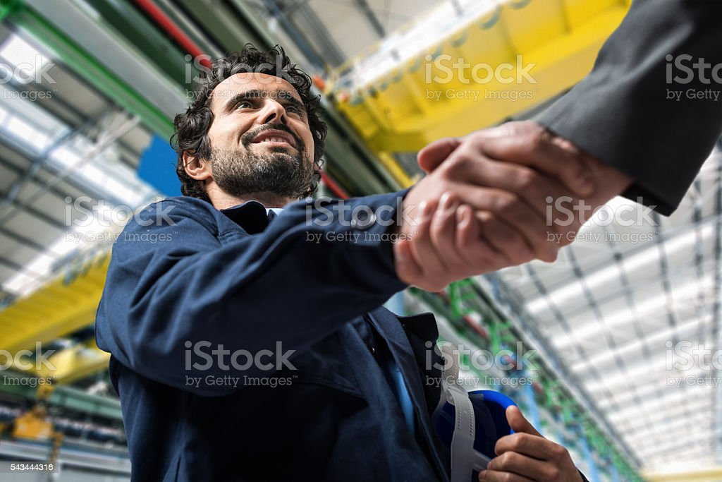 Men shaking hands in an industrial facility stock photo
