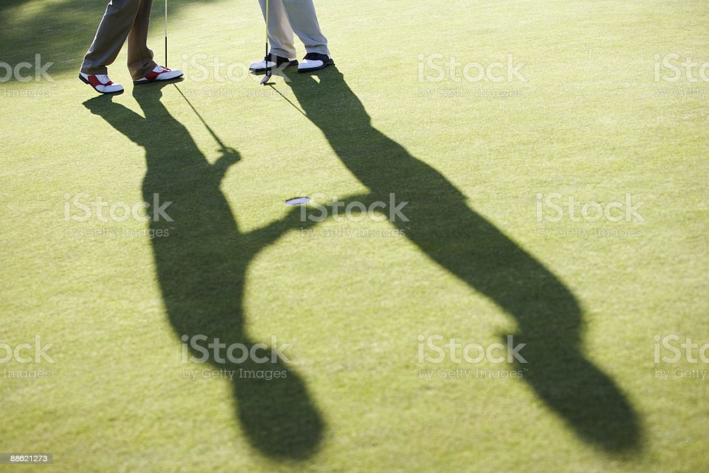 Men shaking hands on putting green stock photo