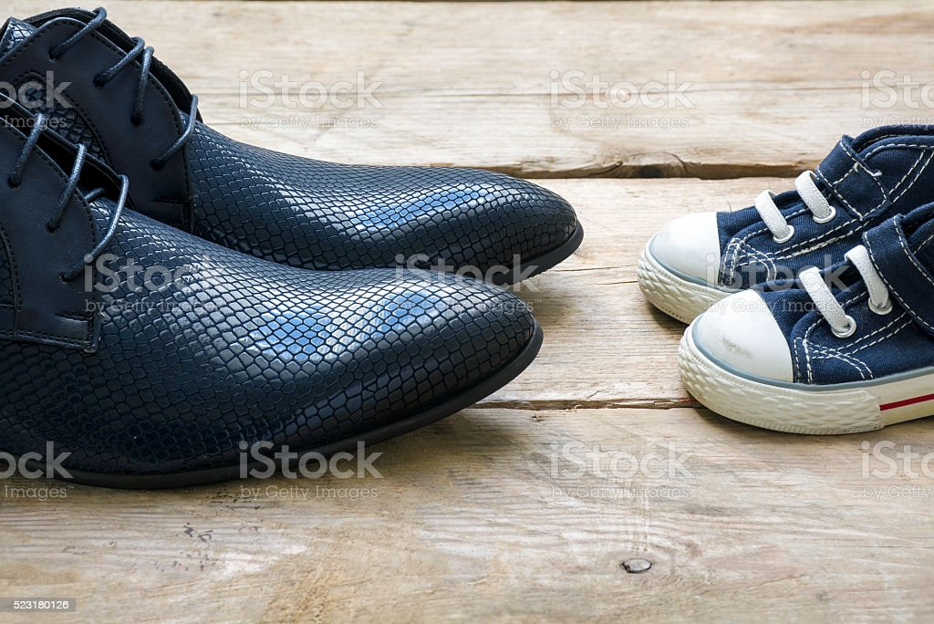men shoes and kids sneakers facing each other, father's day stock photo