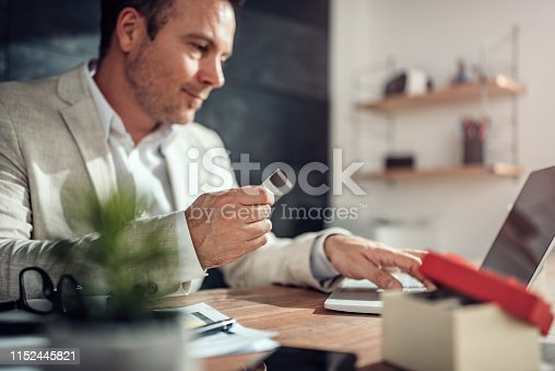 istock Men shopping online and using credit card 1152445821