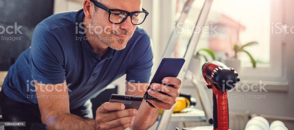 Men shopping online during kitchen renovation stock photo