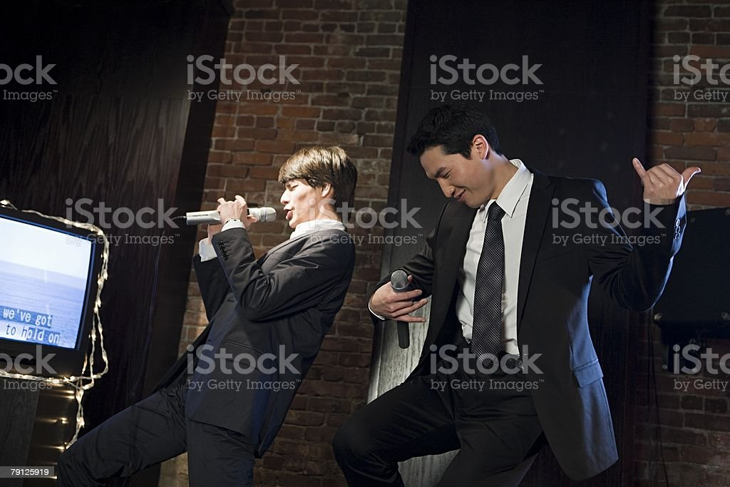 Men singing karaoke stock photo