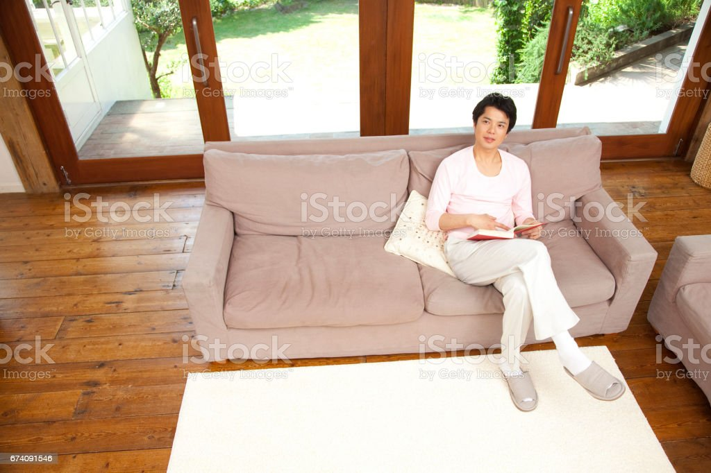 Men sit on the couch in the living room royalty-free stock photo