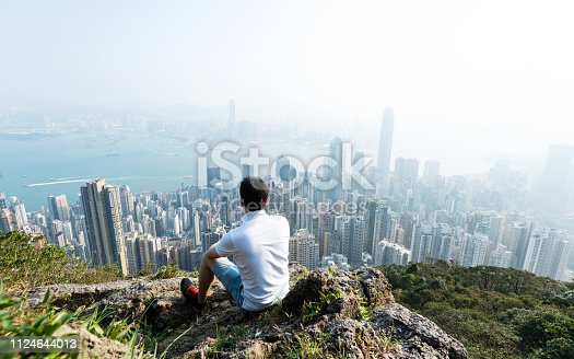 Men sitting on the top of mountain and looking cityscape.