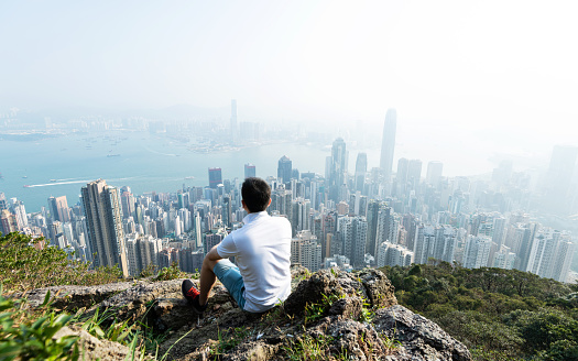 Men sitting on the top of mountain and looking cityscape