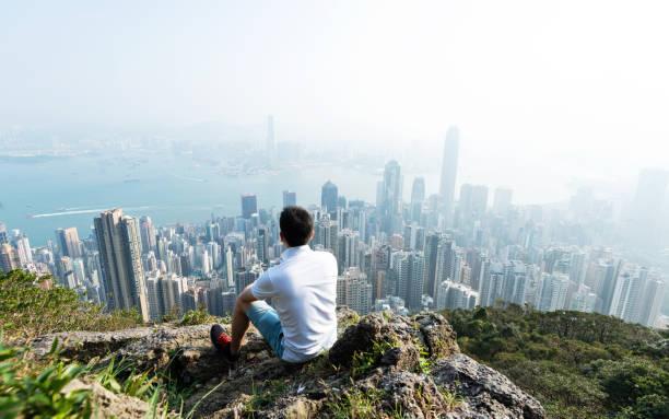 hombres sentados en la cima de la montaña y mirando el paisaje urbano - viaje a asia fotografías e imágenes de stock