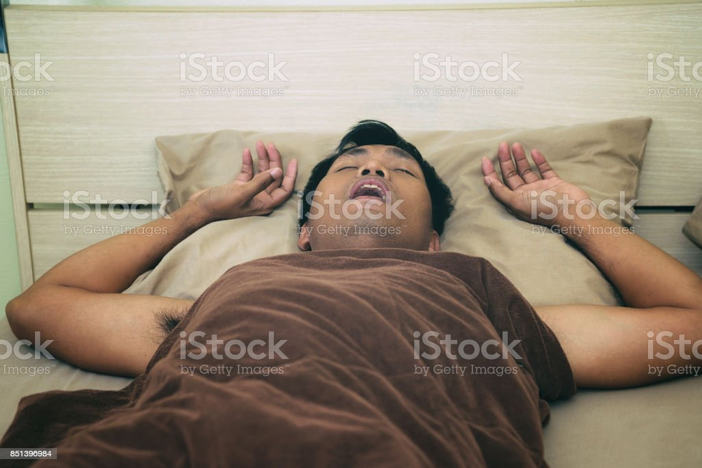 Men sleep and snore loudly in the bedroom. stock photo