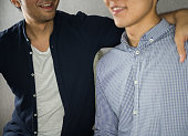 istock 2 men smiling and shoulder hug close up 923605758