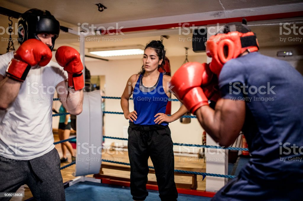 Men Sparing in the Boxing Ring Wearing Protective Head Gear stock photo