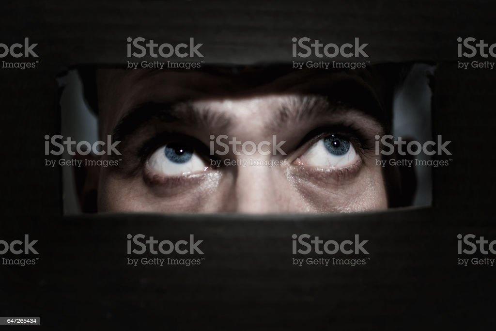 Men  spying through a hole stock photo