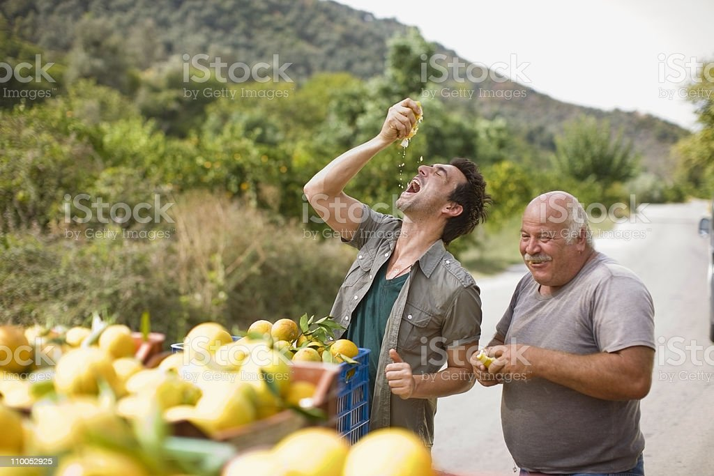 Men squashing oranges stock photo