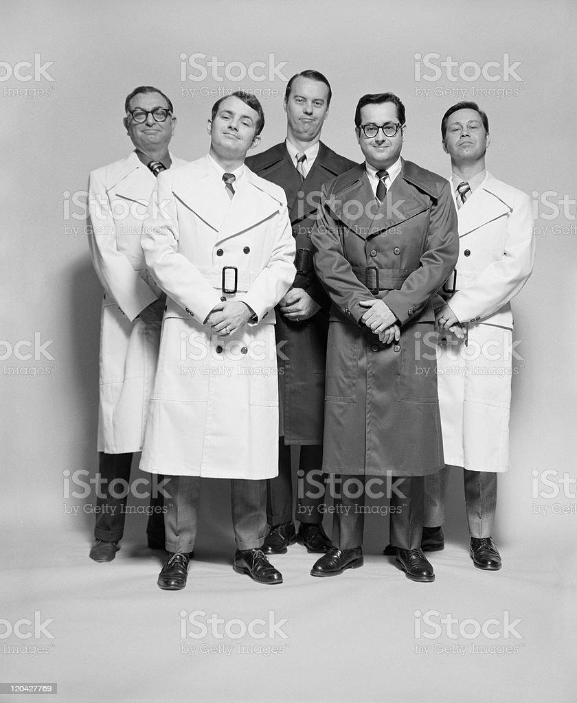 Men standing against white background, smiling, portrait  stock photo