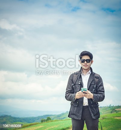 1066358064 istock photo Men standing looking at camera with sunglasses with nature tranquil scene relax looking at view on top of hill 1067463058