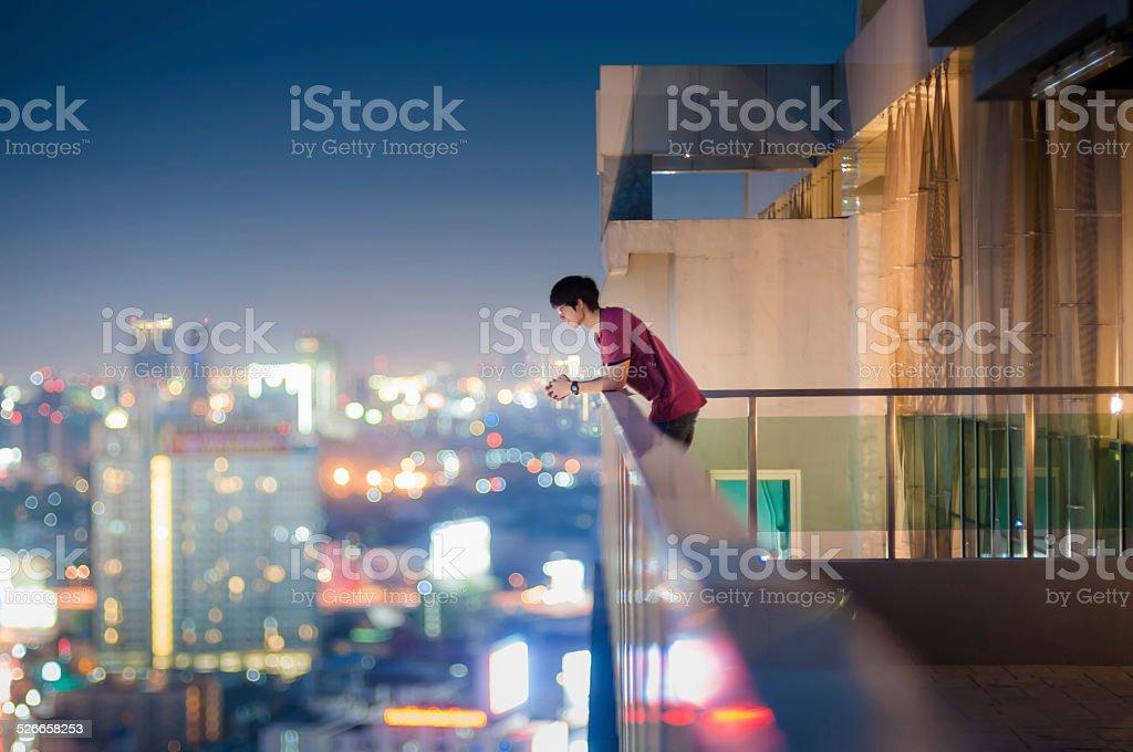 Homem de pé no telhado de um arranha-céu acima da cidade - foto de acervo