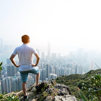 Men standing on the top of mountain and looking cityscape