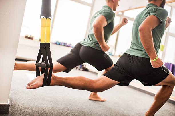Hombres de estiramiento sus piernas en equipos de ejercicios de Pilates. - foto de stock