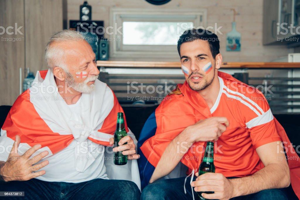 Homens de apoio nacionais diferentes equipes assistindo jogo de futebol - Foto de stock de Adulto royalty-free