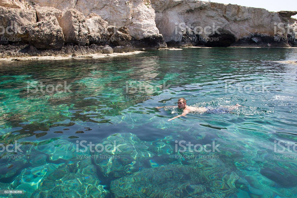 Men swimming in the clear lagoon of the Mediterranean Sea stock photo