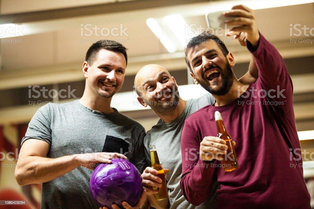 Men taking selfie in bowing alley stock photo