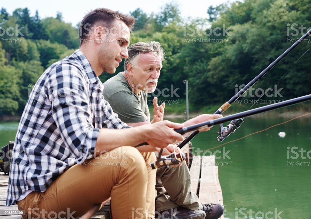 Men talking and fishing together stock photo