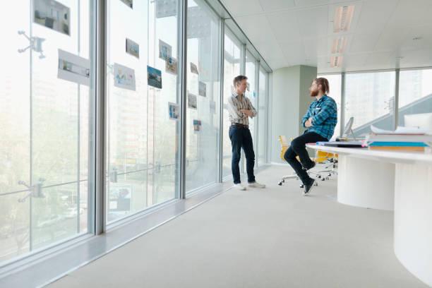 mannen praten in design office vergaderzaal - groothoek stockfoto's en -beelden