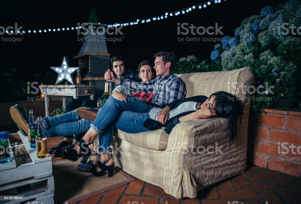 Men talking in party and woman lying on sofa stock photo