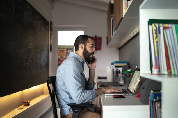Men talking on the phone while working from home stock photo