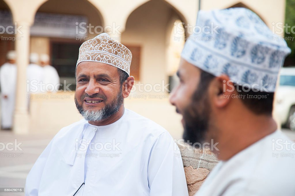 Men talking outside and looking friendly, Nizwa, Oman stock photo