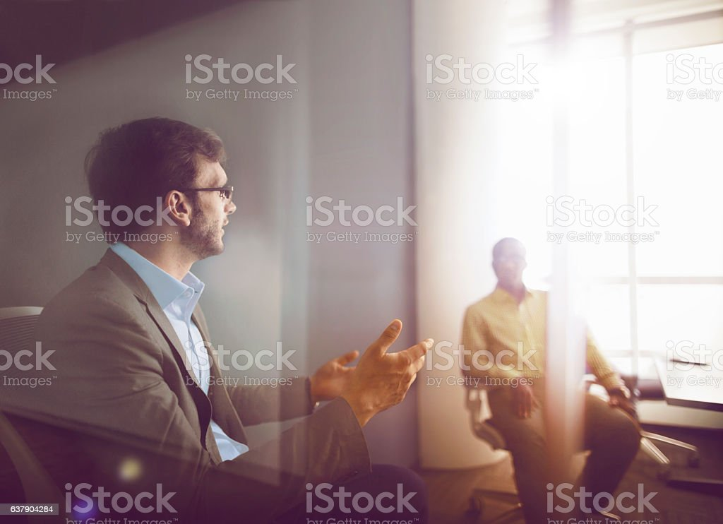 Men talking together in business office meeting stock photo