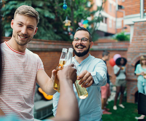 Men Toasting At Barbecue Party. stock photo