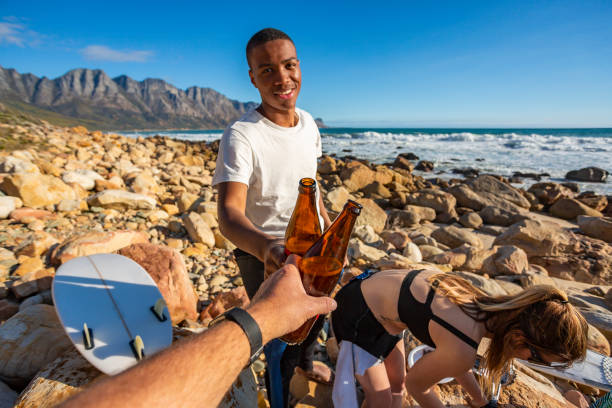 POV of Men Toasting With Beers After a Surf Together stock photo