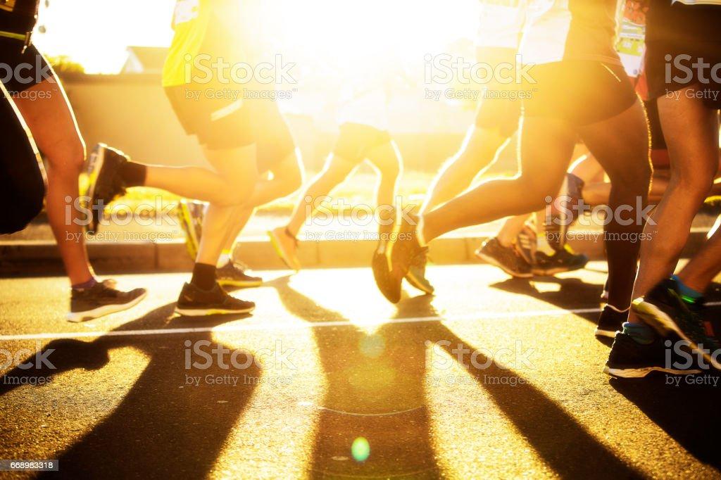 Men train for marathon at dawn with sun behind stock photo
