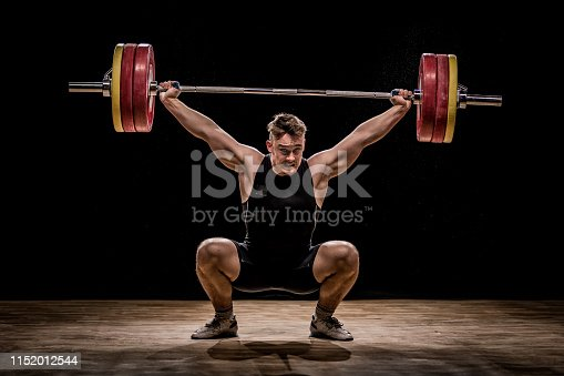 Crouching body builder holding barbells performing deadlift in front of a black background.