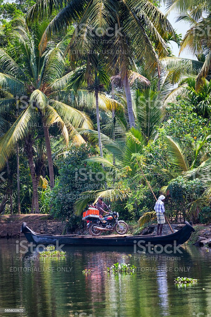 Men transporting motorcycle by Kettuvallam across the Kerala Backwaters, India stock photo