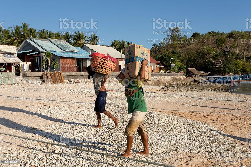 Men transports cargo from ship stock photo