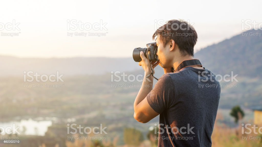 Men travel and take a photo of the sunset. stock photo