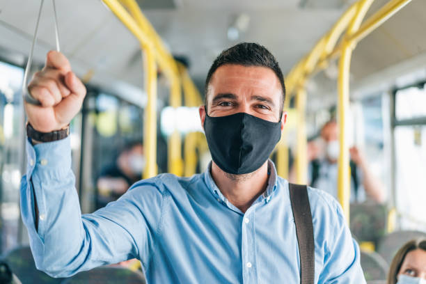 Men traveling in the bus smiling behind the mask, during COVID-19.Everything will be fine