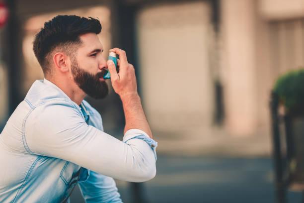 män som använder astmainhalator utomhus - astmatisk bildbanksfoton och bilder