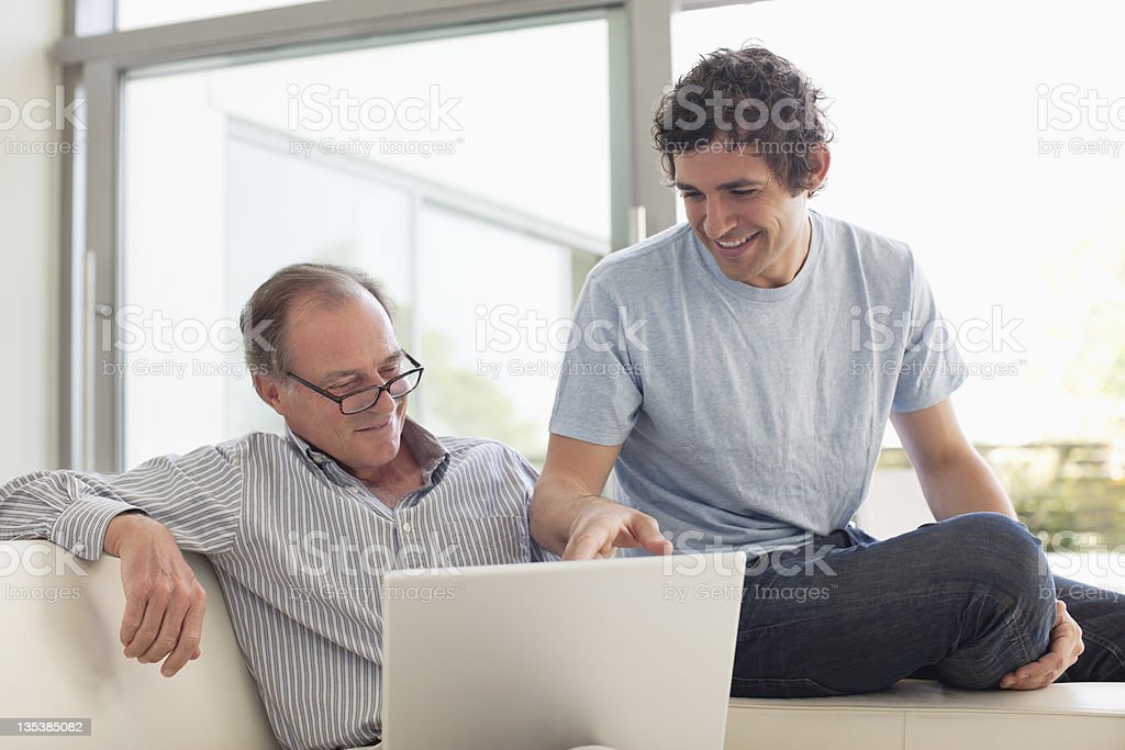 Men using laptop together stock photo