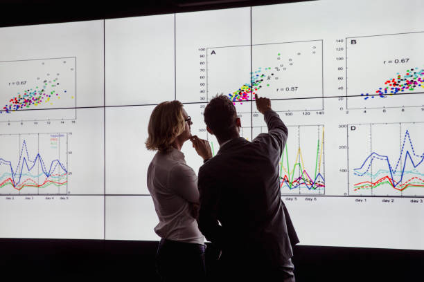 Men Viewing a Large Screen of Information Business men in a dark room standing in front of a large data display data stock pictures, royalty-free photos & images