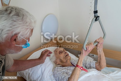 istock Men visiting senior woman lying in bad in nursing home 1280780026