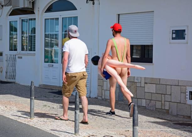 Men walking along a town street, Albufeira. - foto stock
