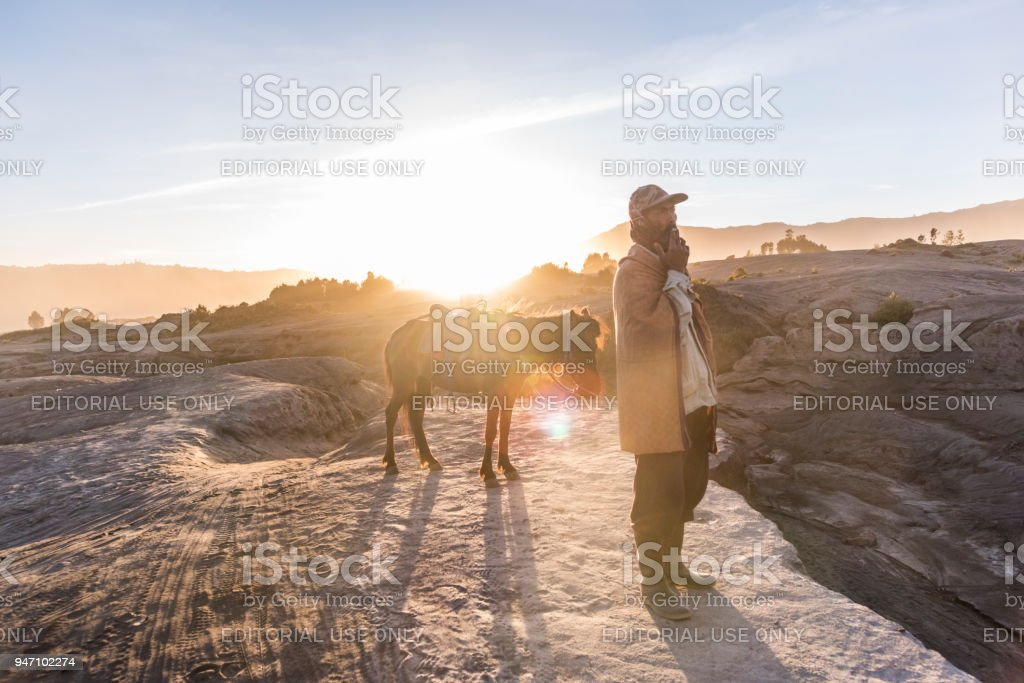 Men walking in Mount Bromo looking for tourist with his horse at sunset, Indonesia stock photo