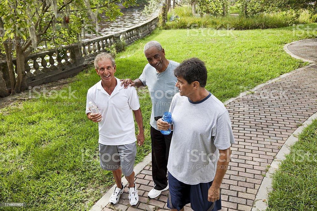 Men walking in park after exercising stock photo