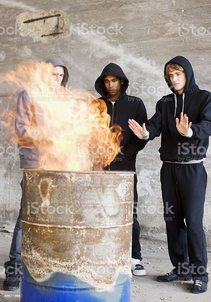 Men warming hands at fire in barrel royalty-free stock photo